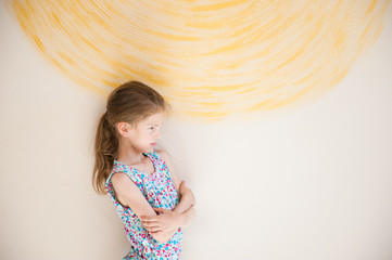 frustrated small girl with grimace on her face near yellow wall mental health