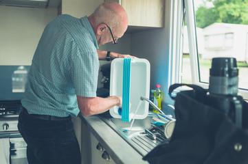 Senior man in caravan cleaning his cooler box