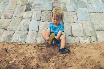Little toddler on beach putting on shoes