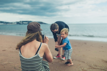 Two women and a toddler are having fun on the beach