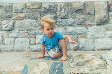 Little toddler by a stone wall