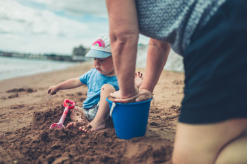 Grandmother helping grandchild build sand castle