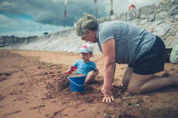 Grandmother helping grandchild build sand castle