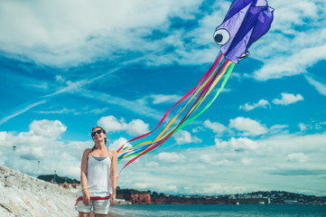 Young woman flying kite on the beach