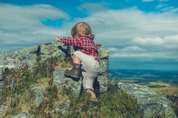 Little toddler climbing rock on the moor