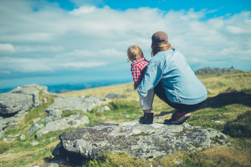Young mother and toddler admiring view from rock on hill