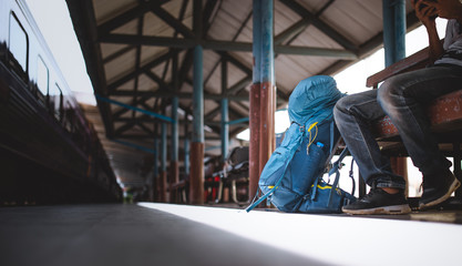 Traveler are backpacking and sitting alone at train station...