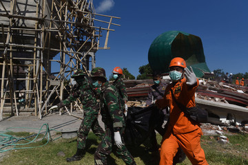 Soldiers and rescue workers remove the body of a victim recovered from a collapsed mosque following Sunday's earthquake in Tanjung, North Lombok