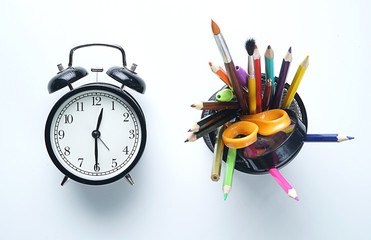 Alarm Clock and School Stationary in Basket on White Background