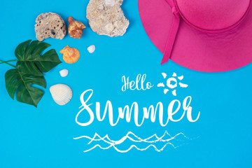 Hello Summer text on blue background, Pink hat with green tropical palm leaf and shell. Beach accessories