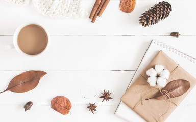 Autumn or winter composition. Cup of coffee, gift, dried autumn leaves, knitted blanket on white wooden background. Flat lay, top view, copy space