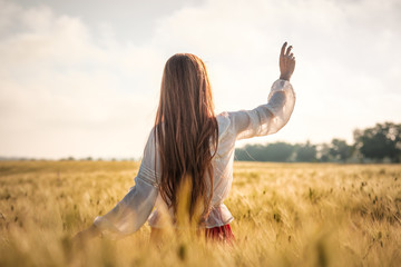Red-haired girl in a wheat field at sunset.