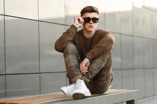 handsome fashion man with sunglasses in military pants and a sweater with white sneakers sits on a bench in the street