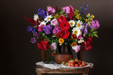 Bouquet of cultivated garden flowers and strawberries.