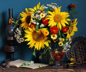 Still life with sunflowers and garden berries: gooseberry and currant.