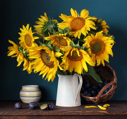 Sunflowers and plums. Still life with flowers and berries.