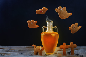 Halloween drink in jar with flying cookies on a black background