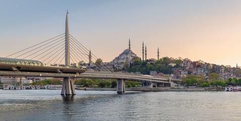 Golden Horn Metro Bridge (Halic Bridge) overlapping Suleymaniye Mosque before sunset, Istanbul, Turkey