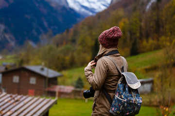Beautiful girl photographer taking photos in the Swiss mountains. Switzerland.