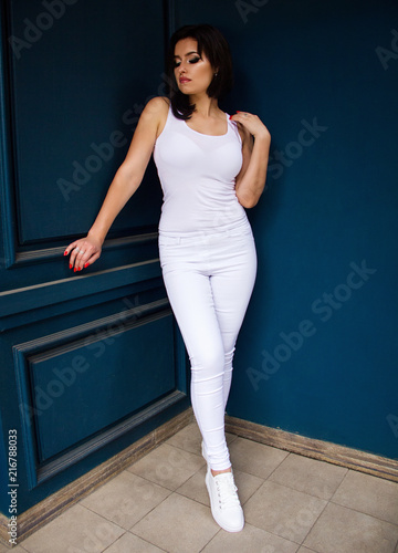 403c3006680 young attractive stylish sexy girl in a white tank top and white pants is  standing fashion like model on blue wooden wall background and looking down