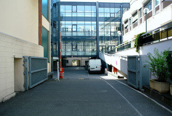 Interior courtyard of a modern building with glass facade and car parking