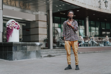 Stylish african american boy on the plaid shirt. Trendy hipster and rapper posed at street. Fashionable black guy. A student walks down the street