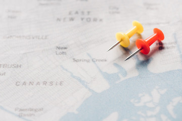 close up view of yellow and red pins on map, traveling concept
