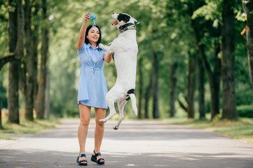 Young beautiful brunette cheerful girl in blue dress have fun and playing with her male white dog outdoor at nature. Nice looking woman loves kind pet. Happy best friends hugs. Domestiic animal smile.