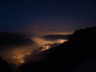 Starry sky and high mountain range, Italian French Alps, mist and fog in the vally with glowing villages below.