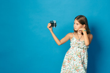 beautiful smiling child (girl) with white teeth holding a camera and making selfie