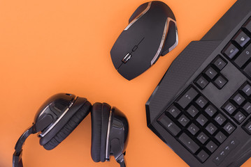 Black mouse, the keyboard, the headphones are isolated on a orange background, the top view. Flat lay gamer background.Workplace with a keyboard, mouse and headphones on a orange background.Copyspace