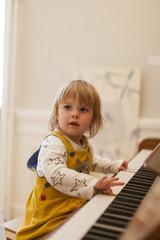 Kleines kind spiel am Klavier. Little child playing on the piano.