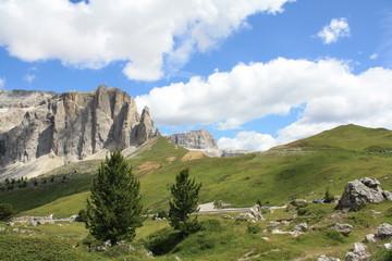 Bergpanorama in den Alpen mit grünen Wiesen vor blauem Himmel und weißen Wolken