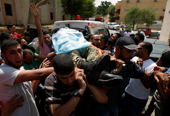People carry the body of a Palestinian Hamas militant who was killed in Israeli tank shelling, at a hospital in the northern Gaza Strip
