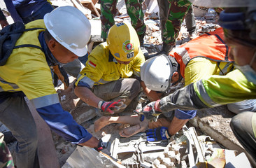 Rescue workers extract a woman, who survived after being trapped in rubble since Sunday's earthquake, in Tanjung
