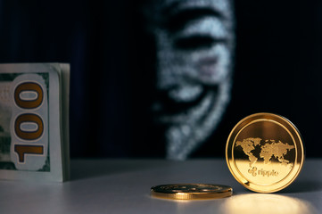 Ripple XRP coins and american dollars with Anonymous hacker face mask on background. Cryptocurrency security concept