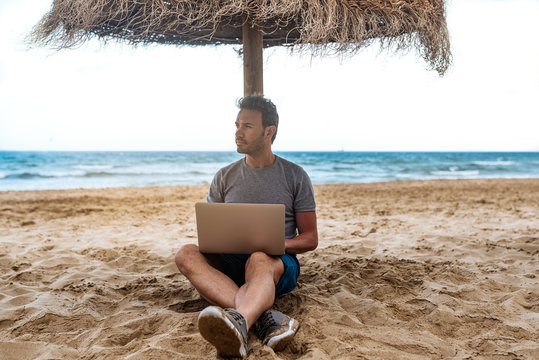 man leaning on a straw umbrella at the beach with laptop
