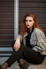 Beautiful young model woman in fashionable jacket and black T-shirt with pants sitting on the street near the gate