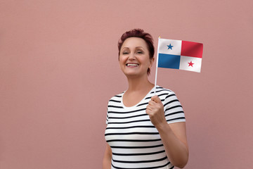 Panama flag. Woman holding  Panamanian flag. Nice portrait of middle aged lady 40 50 years old with a national flag over pink wall background outdoors.