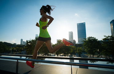 Healthy lifestyle fitness woman runner running on sunrise city
