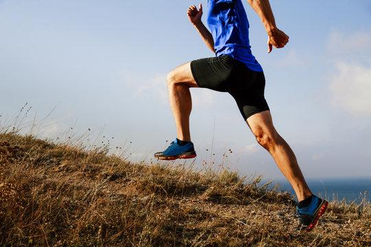 man athlete runner explosive running uphill on trail