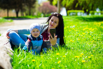 Young mother with phone and little child lies in glade of dandelions