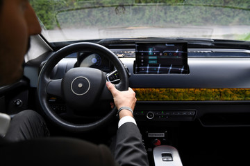 "An employee of German solar car company Sono Motors holds the steering wheel of the prototype car ""Sion"" in Munich"