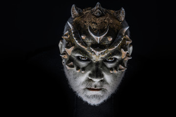 Alien, demon, sorcerer makeup. Head with thorns or warts, face covered with glitters, close up. Fantasy concept. Demon on serious face, black background. Senior man with beard, with monster makeup.