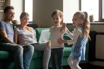 Happy active kids boy brother and girl sister laughing having fun together, cute children siblings playing funny game in living room, parents relaxing with laptop, family cozy weekend at home concept