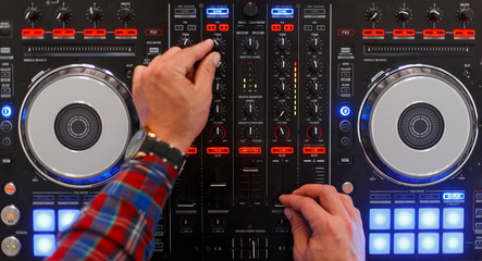 DJ in the process of work. Men's hands are played on the mixing console. Top view