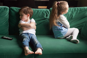 Upset siblings boy and girl sulking sitting with arms crossed on sofa not talking, kids brother...