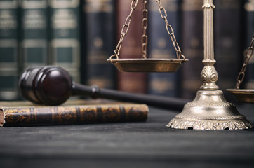 Judge Gavel , Law books and Scales of Justice on a black wooden background.