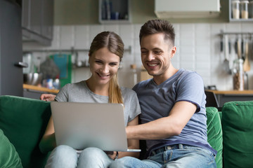 Happy millennial couple laughing looking at laptop screen together enjoying online humor, smiling young man and woman having fun at home on sofa using computer watching funny video in social networks