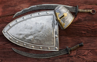 Medieval shield and sword on a wooden background